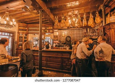 SEVILLE, SPAIN - NOV 15: Bar and tapas cafe with people drinking and eating under dry-cured ham legs and wooden vintage decor on November 15, 2018. Population of Sevilla is near 750,000