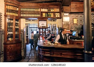 SEVILLE, SPAIN - NOV 15: Bartender busy at bar counter of wine bar with wooden vintage decoration on November 15, 2018. Population of Sevilla is near 750,000