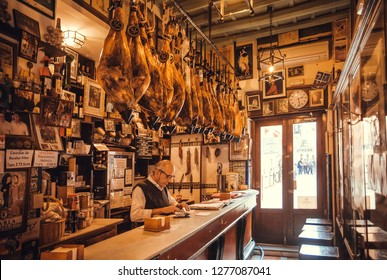 SEVILLE, SPAIN - NOV 15: Elderly waiter of restaurant working at bar counter in retro style place with traditional dry-cured ham legs on November 15, 2018. Population of Sevilla is near 750,000