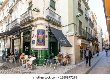 SEVILLE, SPAIN - NOV 15: Elderly people having dinner outside restaurant with colorful sign Bar Europa on November 15, 2018. Population of Sevilla is near 750,000