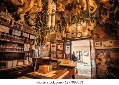 SEVILLE, SPAIN - NOV 15: Entrance to old spanish restaurant in retro style with traditional dry-cured ham legs on wall on November 15, 2018. Population of Sevilla is near 750,000