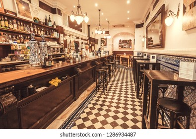 SEVILLE, SPAIN - NOV 15: Old style bar with counter, tile floor and retro furniture waiting for customers and evening on November 15, 2018. Population of Sevilla is near 750,000