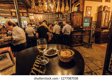 SEVILLE, SPAIN - NOV 15: Wine bar with eating people under dry-cured ham legs and wooden vintage decor on November 15, 2018. Population of Sevilla is near 750,000