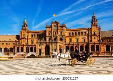 SEVILLE, SPAIN - NOVEMBER 19, 2014:  Touristic horse carriages and central building  at Plaza de Espana. Seville, Spain
