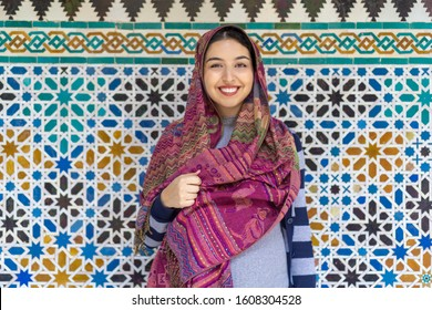 Seville, Spain- November 20th 2019: Pregnant woman with a colorful headscarf/hijab standing in front of a mosaic smiling.