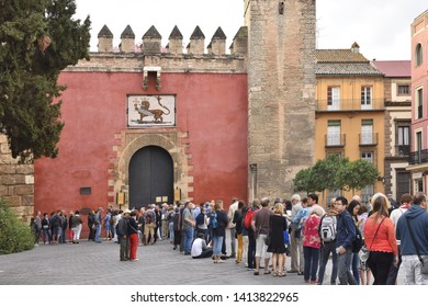 Seville, Spain - October 16, 2016: Tourists queuing outside Gate of Lion - main entrance into Royal Alcazar palace in Seville Spain Europe.