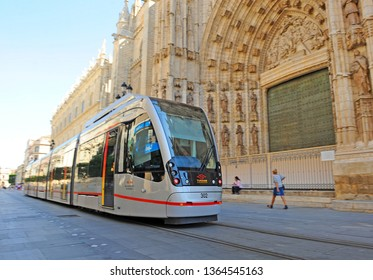 Seville, Spain - Sep 8, 2011: Modern tram along the Avenue of the Constitution circulating in front of the cathedral, in downtown of Seville.