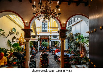 Seville, Spain - Sept 10, 2019: Busy restaurant courtyard in Seville, Spain with traditional Moorish arches