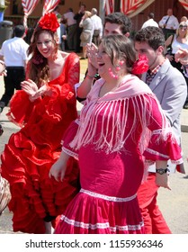 Seville Spain/14th April 2013/ Two young happy women in brightly brightly coloured traditional clothing dance at  the annual April Spring Fair held in the city of Seville Spain