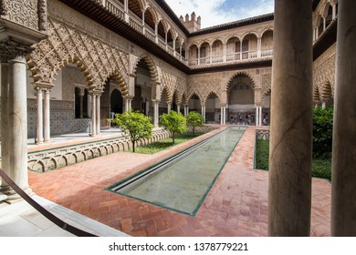 SEVILLE,SPAIN.6/28/2018, A detailed picture of the reflecting pool, columns and arches in the Courtyard of the Maidens or Patio de las Doncellas Courtyard at the Alcazar Palace/ the Royal Alcazar
