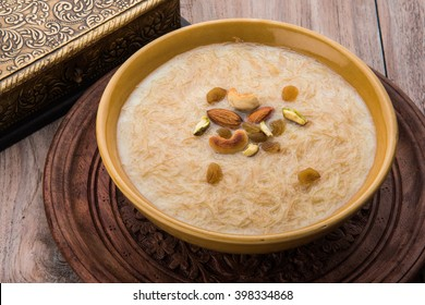 Seviyan / vermicelli kheer / khir, is a popular dessert consumed especially on  Eid or any other festival in india/asia. Served in a bowl dry fruits over colourful/wooden background. Selective focus
