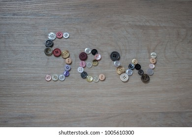 'Sew' spelled out in buttons against a pale wooden background