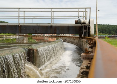 Sewage treatment mechanism spinning and filtering water flow in basin.
