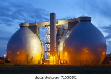 A sewage treatment plant with illumination and night blue sky.