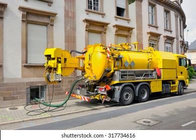 Sewage truck on city street in working process to clean up sewerage overflows, cleaning pipelines and potential pollution issues from an modern building.