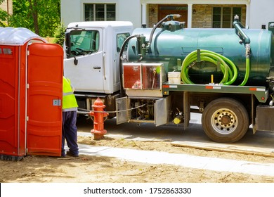 Sewage truck on worker pumping feces out of rental toilet for disposal and cleaning at the construction