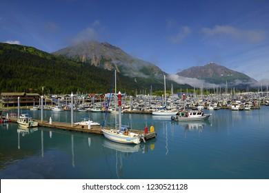 SEWARD, ALASKA - JULY 31, 2018: Boats at a pier in Seward with mountains in background. Seward's Boat Harbor is situated on the northern edge of Resurrection Bay, Alaska, USA