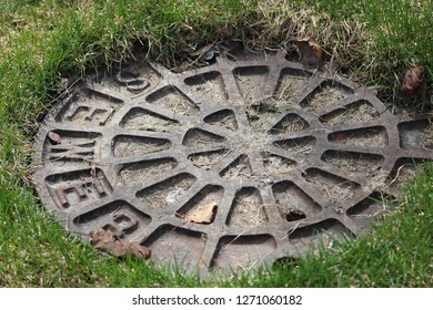 Sewer cover partly hidden