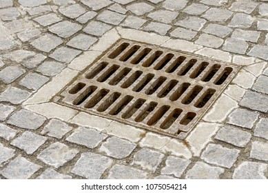 sewer grate for rainwater installed near the road and surrounded by cobblestones
