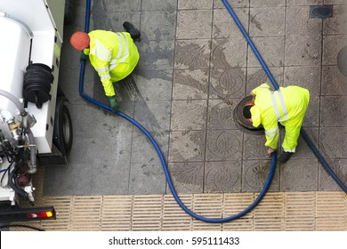 sewer line drainage  by utilities workers with hose with pressurized water