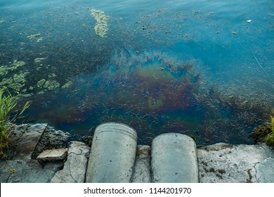 Sewer pipes at shore, stain of oil or fuel on water surface, nature pollution by toxic chemicals, dirty sea concept