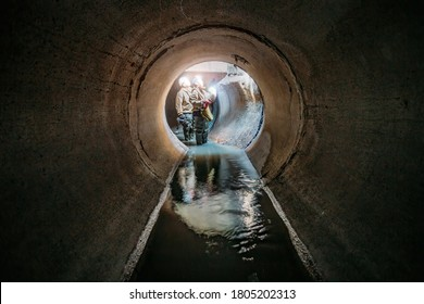 Sewer tunnel workers examines sewer system damage and wastewater leakage