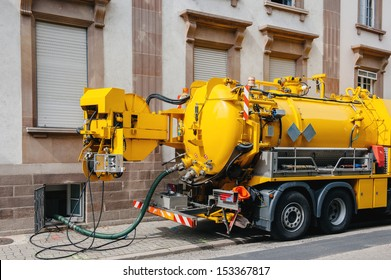 Sewerage truck on street working - clean up sewerage overflows, cleaning pipelines and potential pollution issues from an modern building.