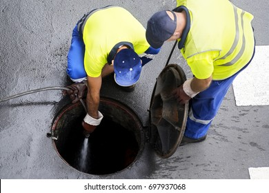 sewerage workers  draining the sewer line