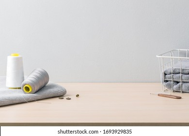sewing accessories and clothing on wood table in gray background.