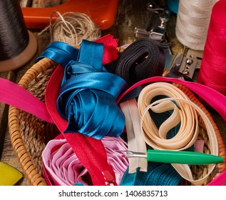 Sewing accessories coil threads and bias tape and seam ripper in basket supplies close up.