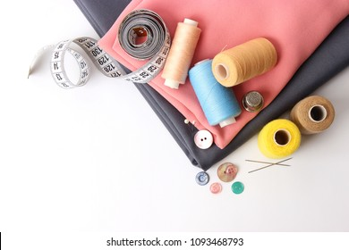 Sewing accessories and fabric on a white background. Sewing threads, needles, pins, fabric, buttons and sewing centimeter.  top view, flatlay