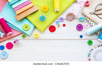Sewing accessories and fabric on a white background. Sewing threads, needles, pins, fabric, buttons and sewing centimeter. Top view, flat lay.