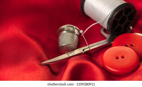 sewing accessories on a background of red fabric