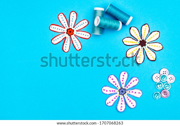 Sewing accessories on a blue background. Sewing threads in blue colors and buttons. Paper cut our flowers. Top view with room for copy.