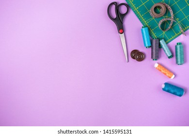 Sewing accessories on a violet background. Sewing threads and needles, scissors, buttons, sewing meter and cutting mat. Top view, flatlay