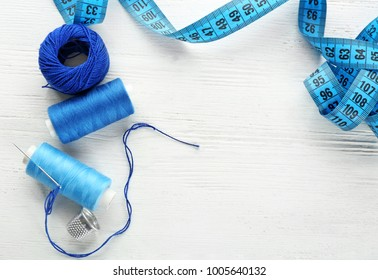 Sewing accessories and threads on table, top view