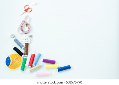 Sewing accessories, tools ,colorful spools, needle and measuring tapeof thread with scissors isolated on white background, top view
