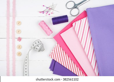 Sewing background. Cotton fabrics, spools of thread, scissors, buttons, measuring tape, sewing supplies. Accessories for sewing on white wooden background. Set for needlework top view