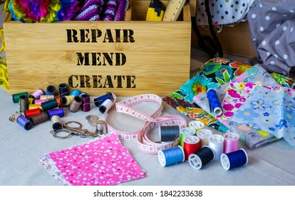 Sewing box with repair, mend and create text surrounded by sewing tools, fabric and thread. Repair and upcycle textiles and clothing to reduce waste and sustainable living.