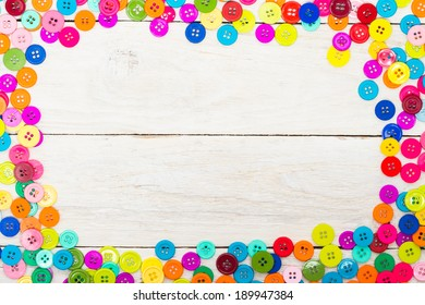 Sewing buttons on a wooden background with copy space
