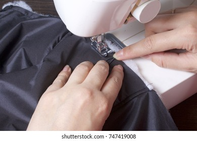 Sewing clothes by an individual entrepreneur. A woman is working on a sewing machine. Staples the cut elements of the product.
