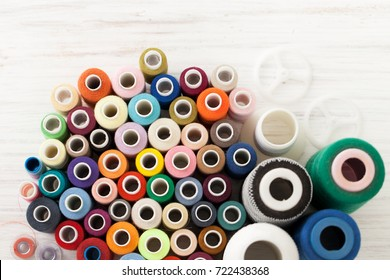 A lot of sewing colored thread on a white table. The view from the top.