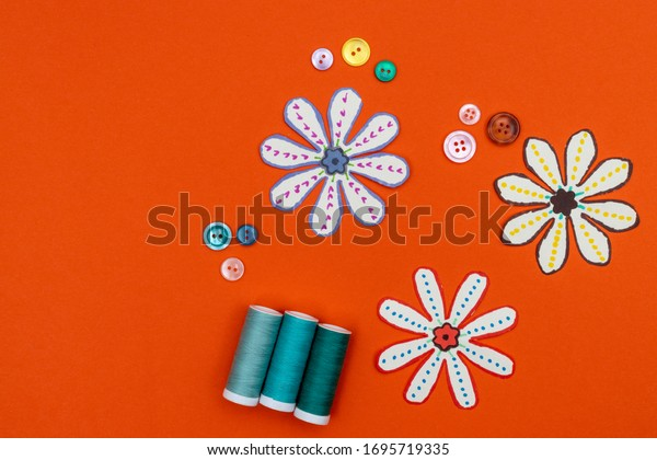 Sewing concept with buttons and thread. Paper flowers on an orange background. Room for copy.