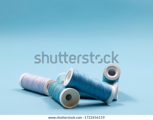 Sewing concept with spools of blue threads on a blue background. Room for copy.