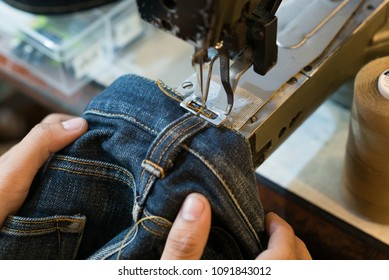 Sewing denim jeans with sewing machine. Repair jeans by sewing machine. Alteration jeans, handmade garment industrial concept.