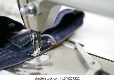 Sewing denim jeans with vintage sewing machine. Repair jeans by sewing machine. Alteration jeans, handmade garment industrial concept.