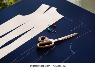 Sewing a dress according to the drawing. Tailoring and items for sewing clothes. Scissors, blue fabric, a pattern is needed for sewing clothes. Cut dresses from costume fabrics.