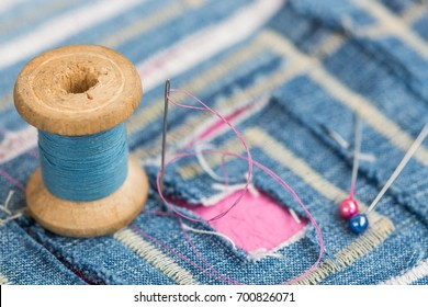 sewing and embroidery concept - close up on spool of blue threads, needle with pins over decorated blue fabric with cuted pattern, macro of stitching and designer decors in the form of labyrinth