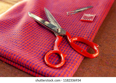 Sewing equipment composition on the table: scissors, needles, fabric. Fashion designers studio