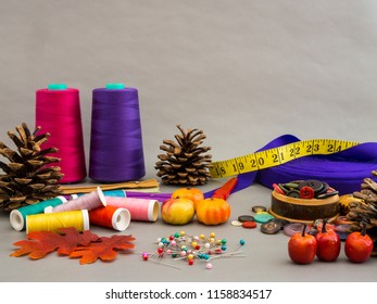 Sewing and fall. An autumn scene with sewing materials, colorful threads, ribbon, tape measure, straight pins. And fall decoration pine cones, pumpkins, leaves and red apples.